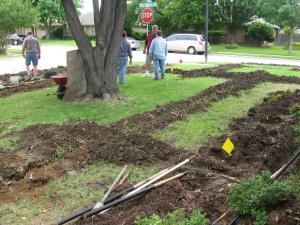 a fully trenched yard with lines being laid